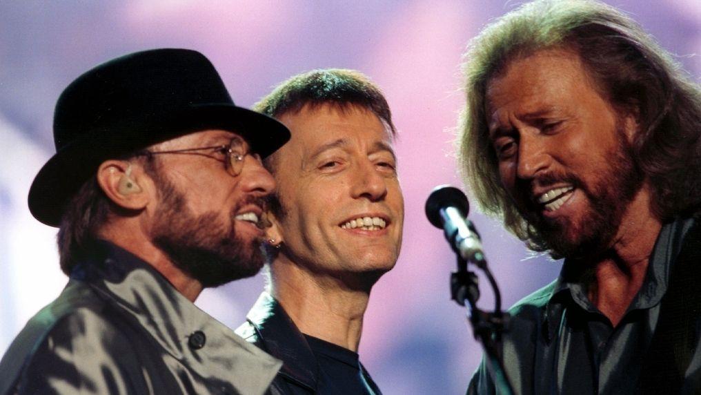 Drei Männer, zwei mit Bärten, der in der Mitte glattrasieret, singen lächelnd in ein Mikrofon vor ihnen.