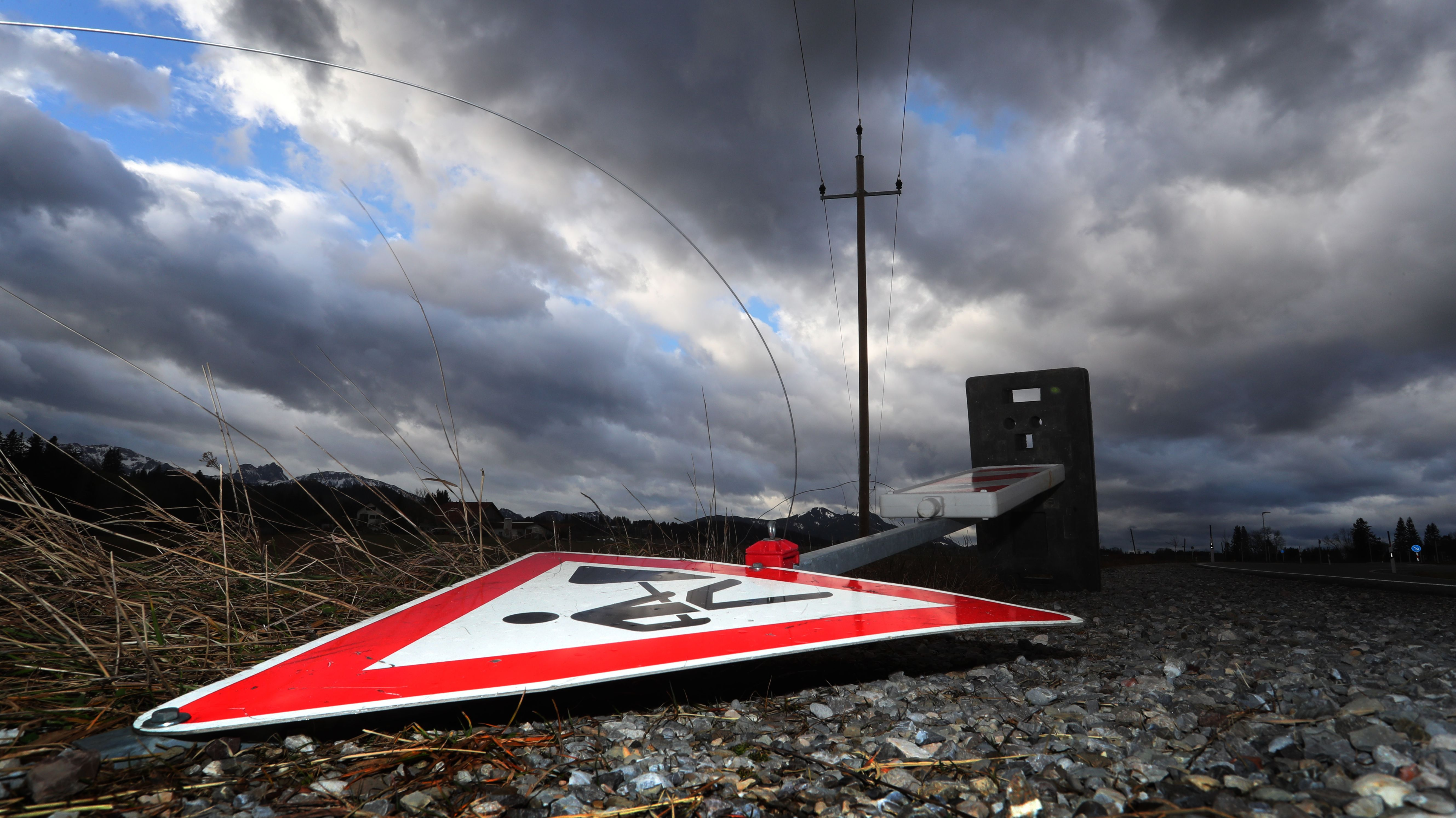 """Bayern, Seeg: Ein Baustellenschild liegt durch das Sturmtief """"Sabine"""" umgekippt unter einem wolkenüberzogenem Himmel auf einer Straße."""