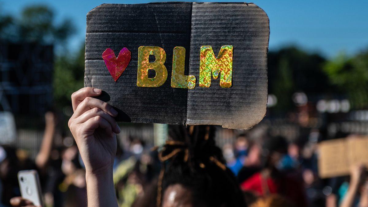 """Protestschild auf dem """"BLM"""" steht."""