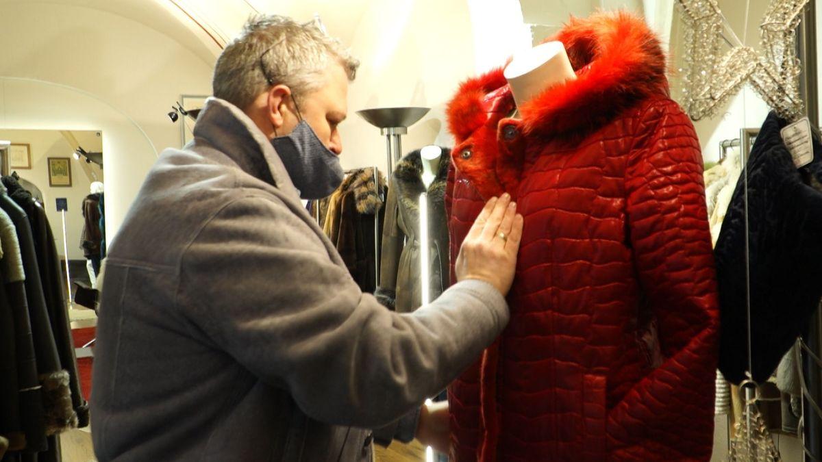 Der Regensburger Pelzhändler Marcus Müller drapiert eine Schaufensterpuppe in seinem Laden.