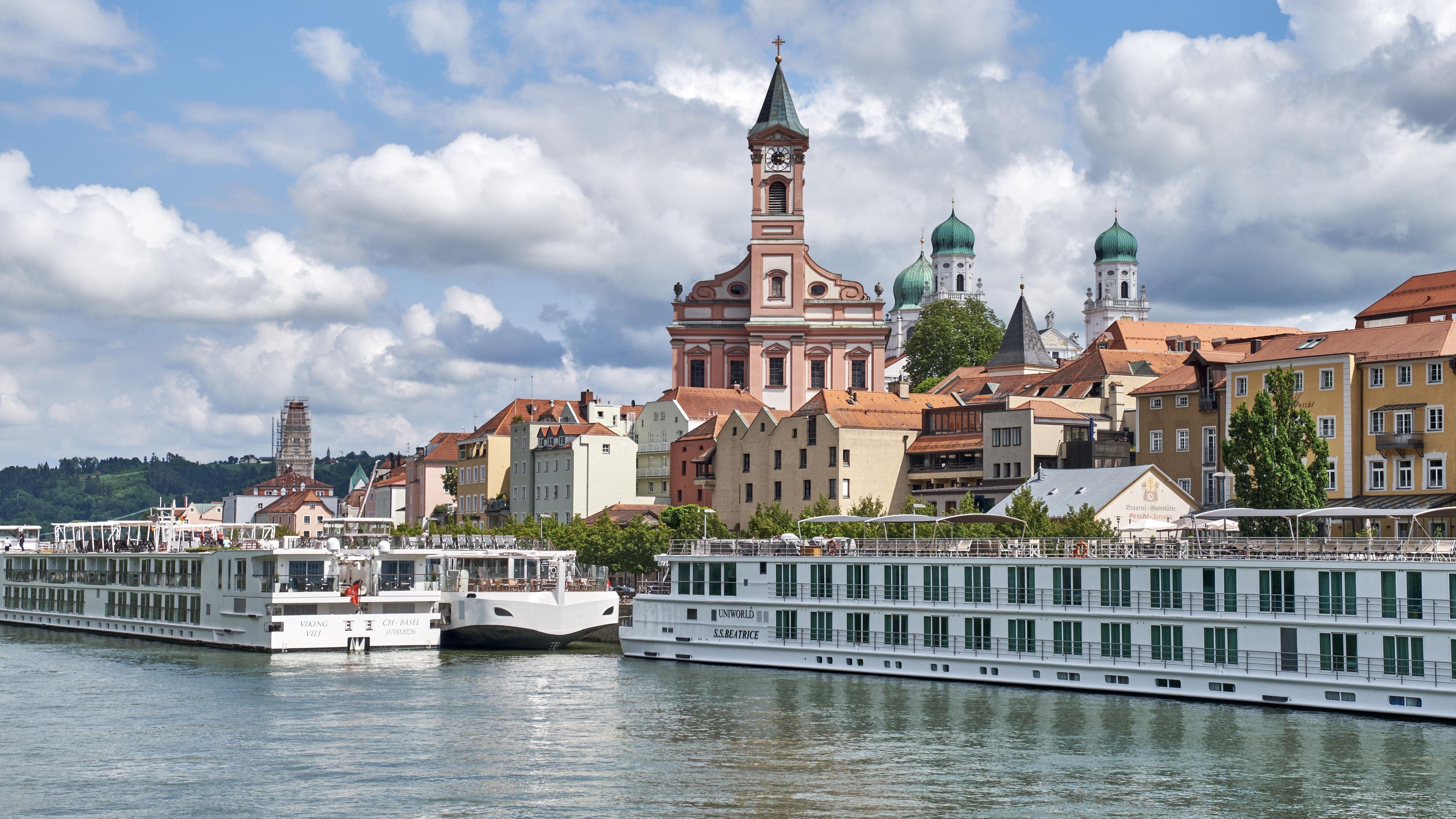 Blick über die Donau auf Schiffsanlegestelle mit Flusskreuzfahrtschiffen, zur Altstadt von Passau.