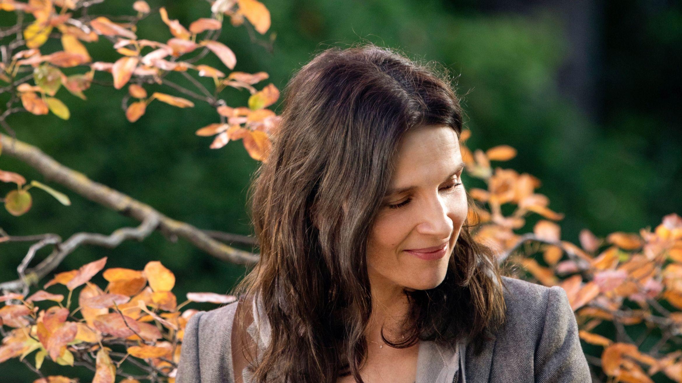 """Szene aus """"La Vérité"""" mit Juliette Binoche, die im Garten vor einem herbstlichen Baum steht."""