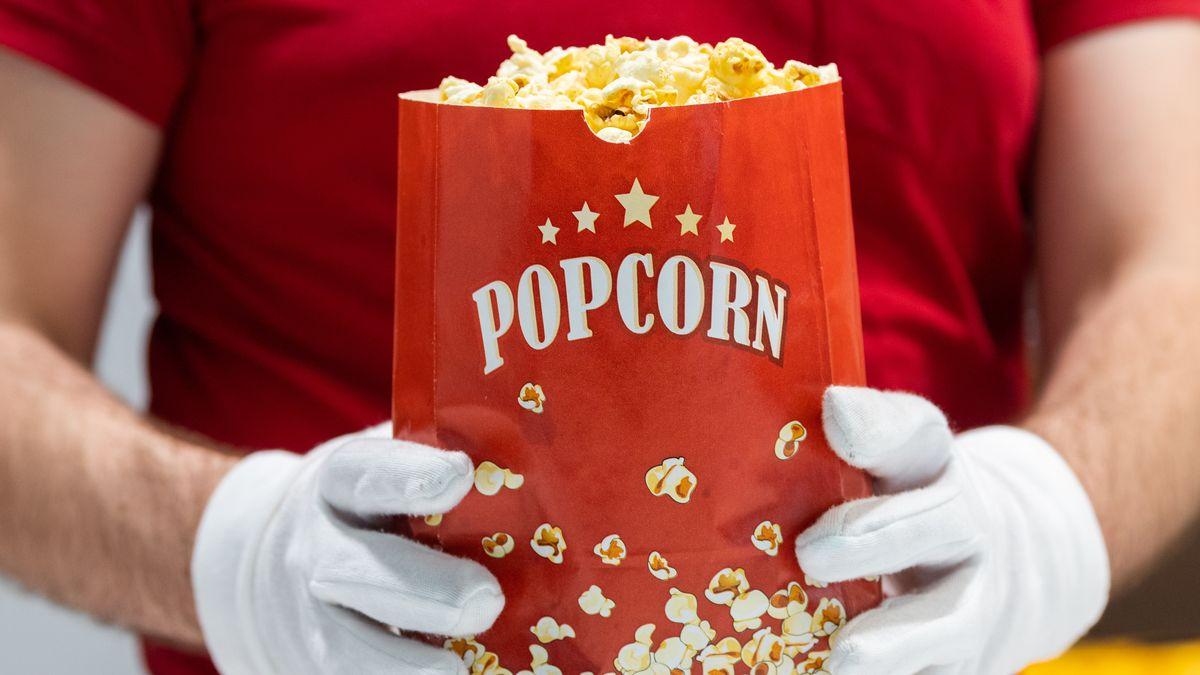 Ein Mitarbeiter eines Kinos hält Popcorn in den Händen und trägt dabei Schutzhandschuhe.