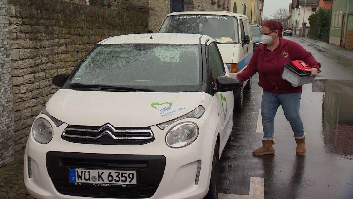 Die Mitarbeiterin eines ambulanten Pflegedienstes aus Unterfranken steigt in ihr Auto ein.