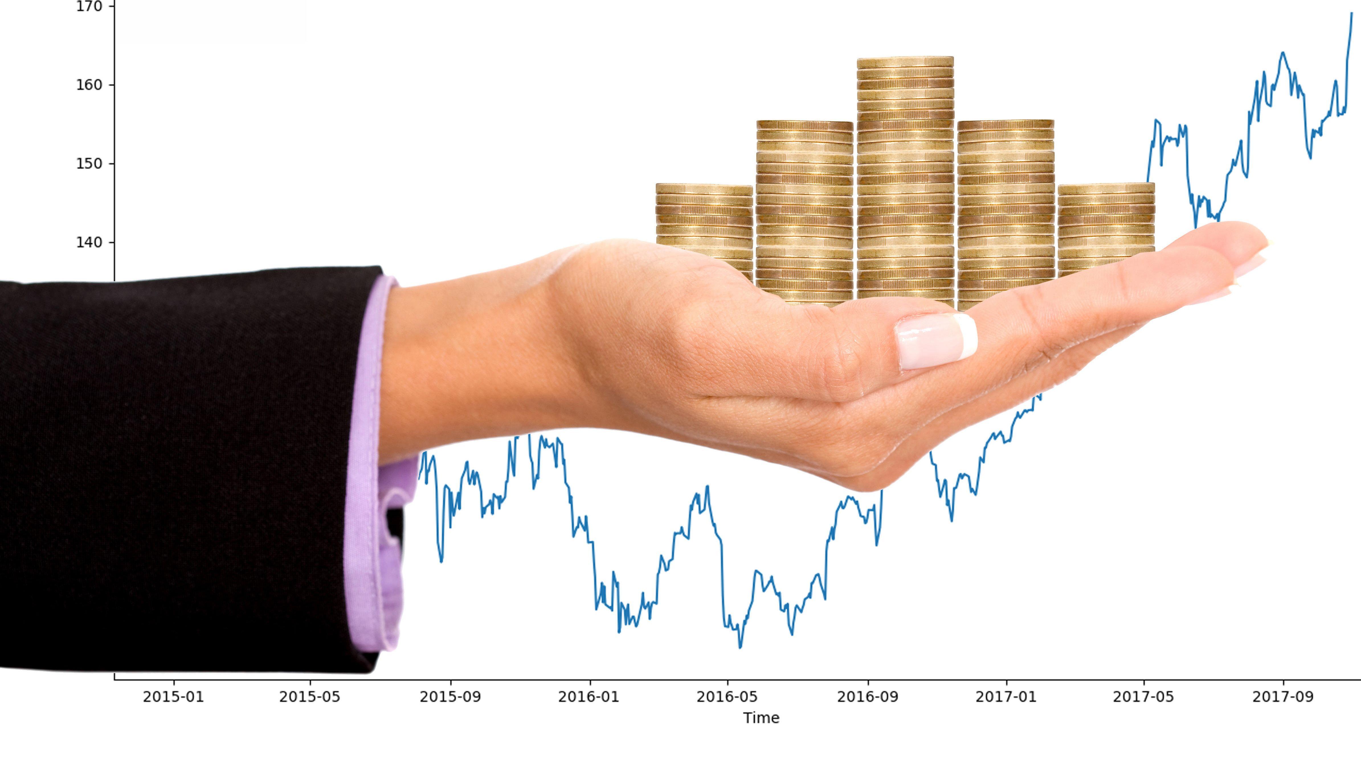 Symbolbild: eine Hand mit gestapelten Münzen vor einem Aktienchart.