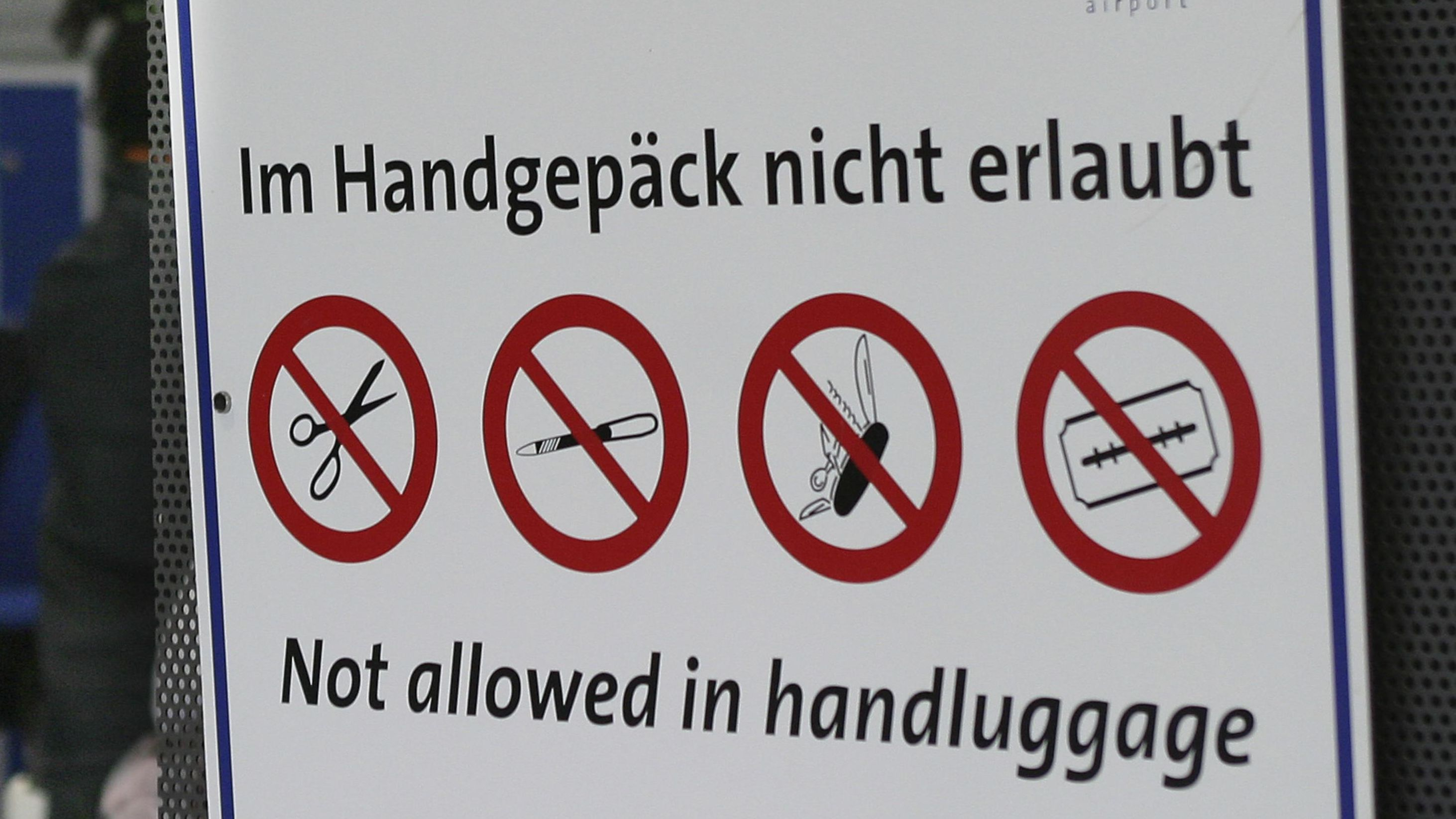 Ein Schild am Flughafen Frankfurt/Hahn zeigt Piktogramme von Dingen, die im Handgepäck nicht erlaubt sind: Nagelschere, Feile, Taschenmesser, Rasierklinge.