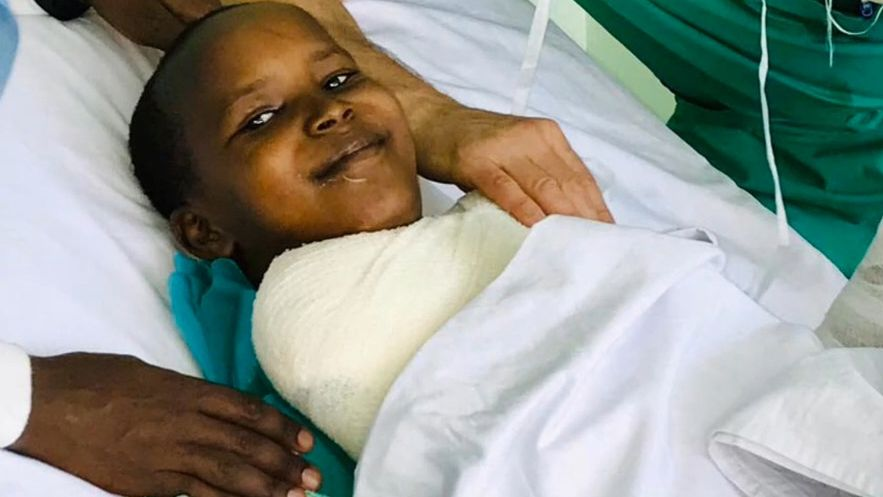 Der schwerverletzte 12-jährige Junge Safari, lächelnd in einem Krankenbett