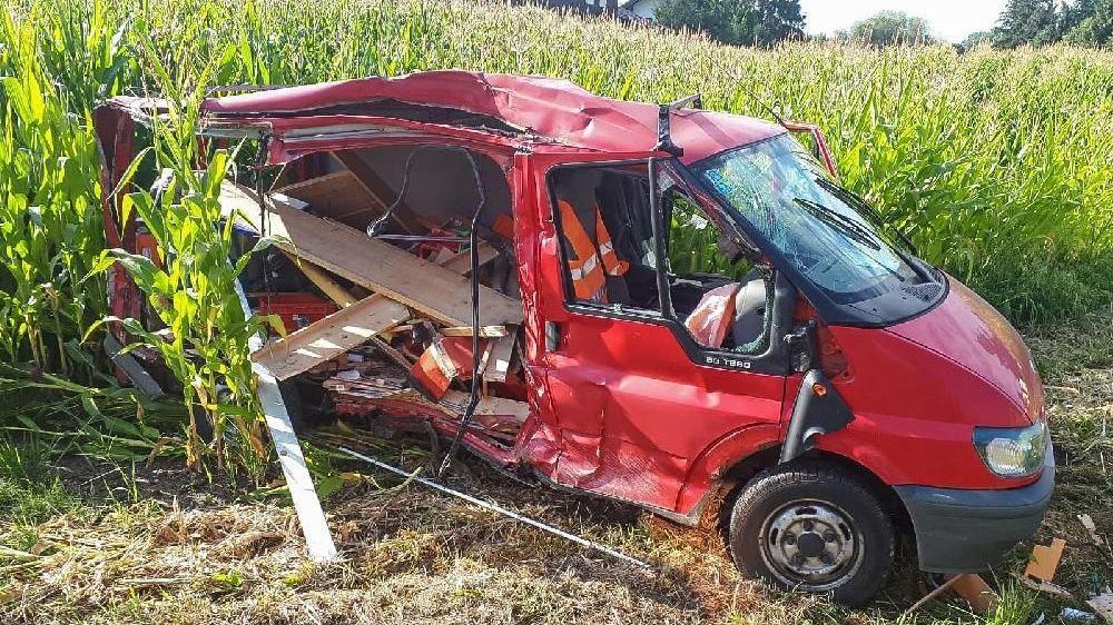 Der Ford Transit Kombi liegt in einem Feld und erlitt Totalschaden