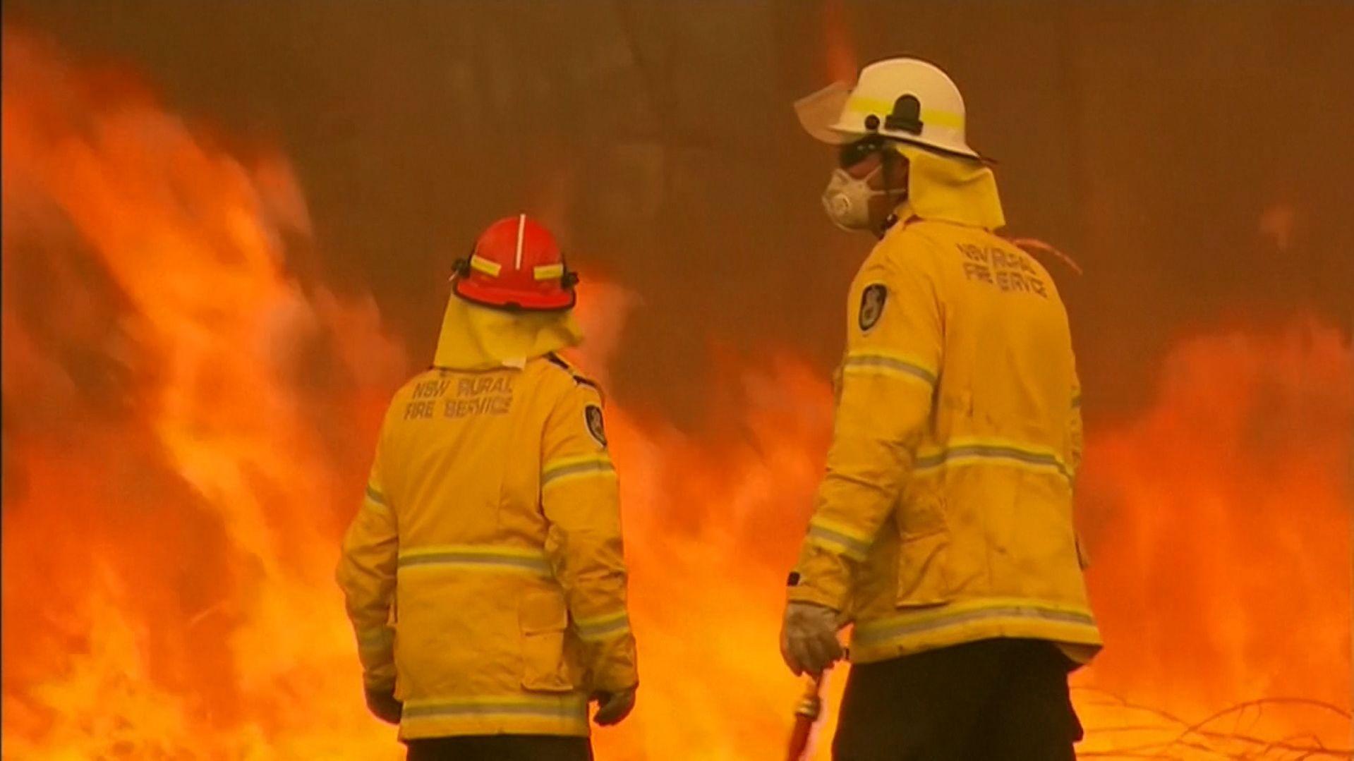 Zwei australische Feuerwehrleute vor einem lodernden Buschfeuer