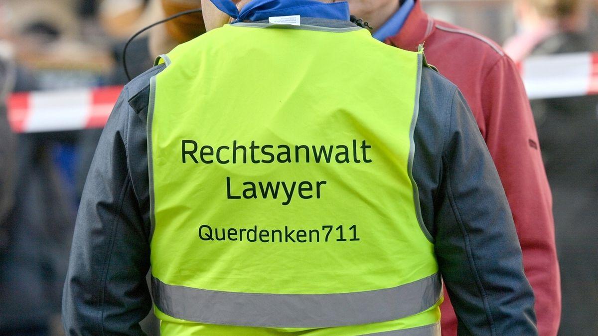 """Ein Demonstrant trägt bei einem Protest am Odeonsplatz eine Warnweste mit der Aufschrift """"Rechtsanwalt - Lawyer - Querdenker 711"""""""