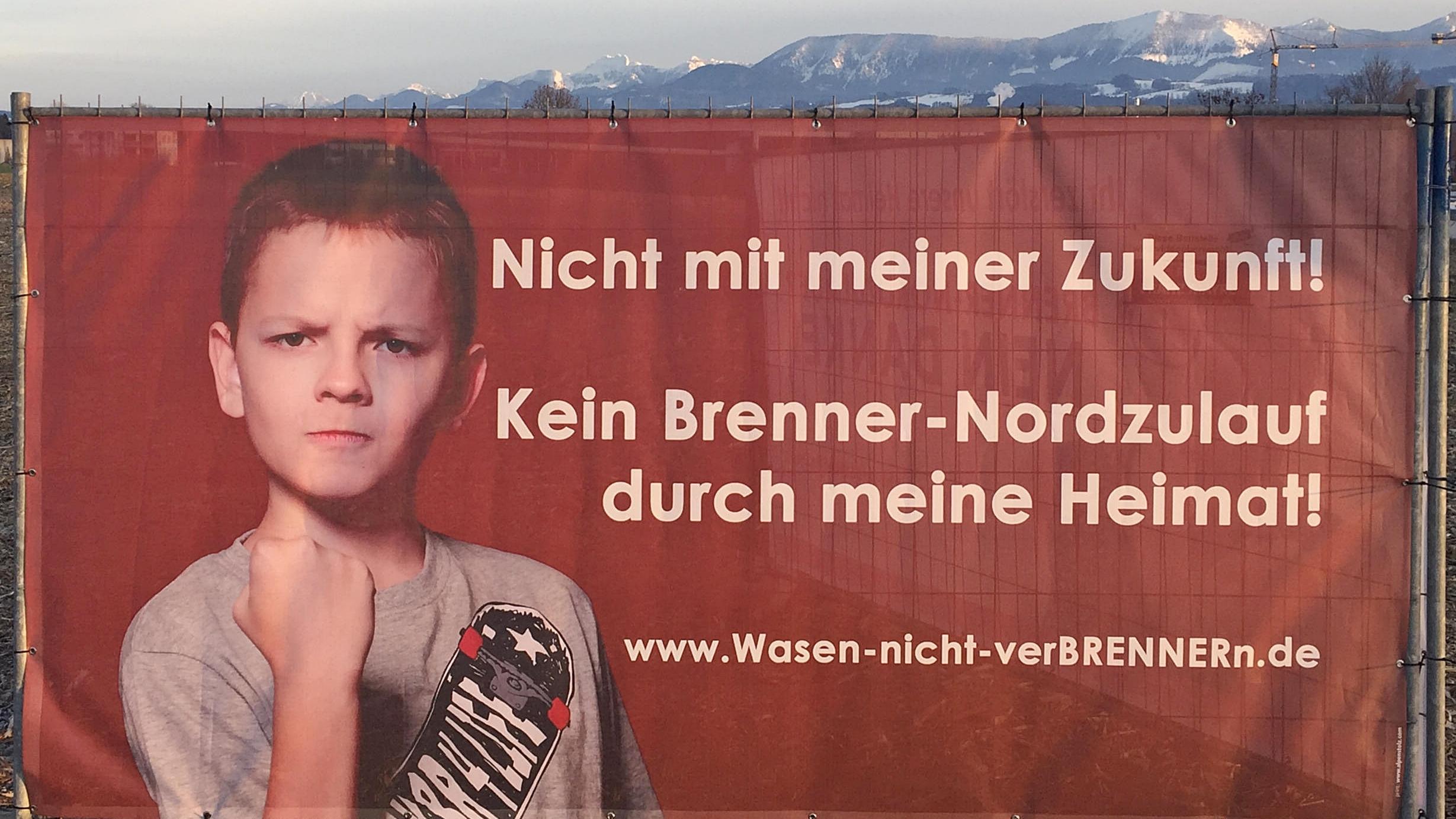 Wie überall im oberbayerischen Inntal stehen oder hängen auch in Rosenheim Protestplakate- und Banner gegen den Brennernordzulauf, hier im Rosenheimer Süden, im Stadtteil Aising. Auch hier könnte die Trasse des Brenner-Nordzulaufs durchgehen. Im Hintergrund rechts die Hochries und links die Kampenwand.