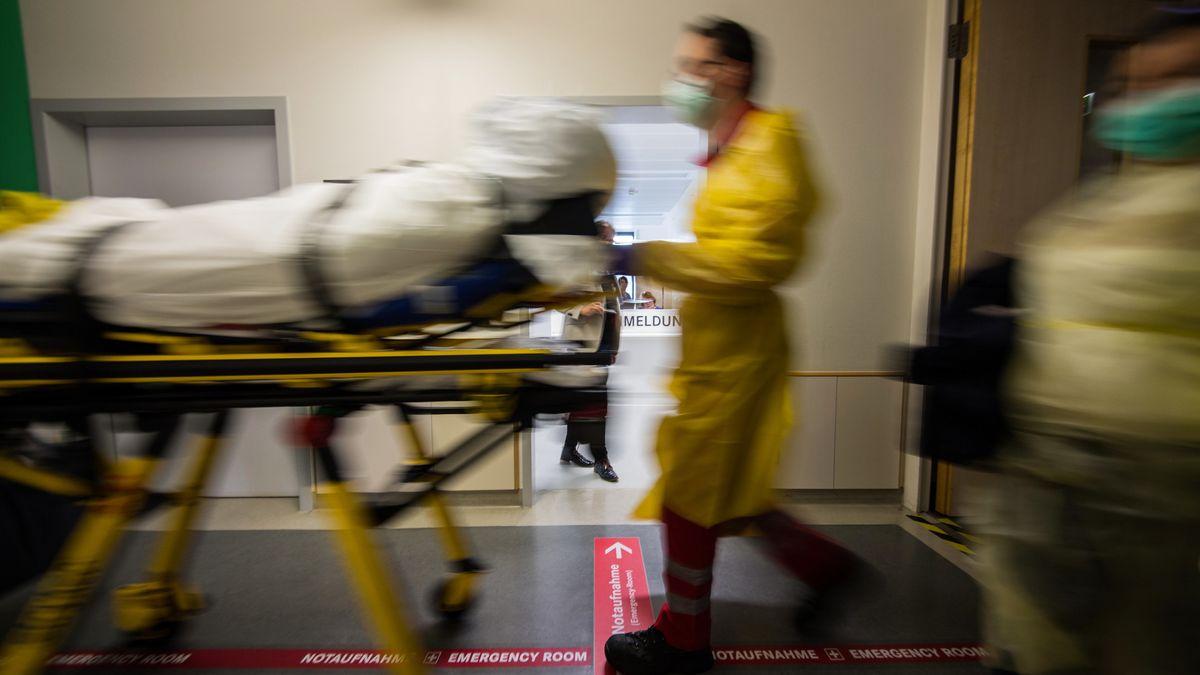 Auf einer Bahre wird ein Patient von einem Sanitäter über einen Gang geschoben.