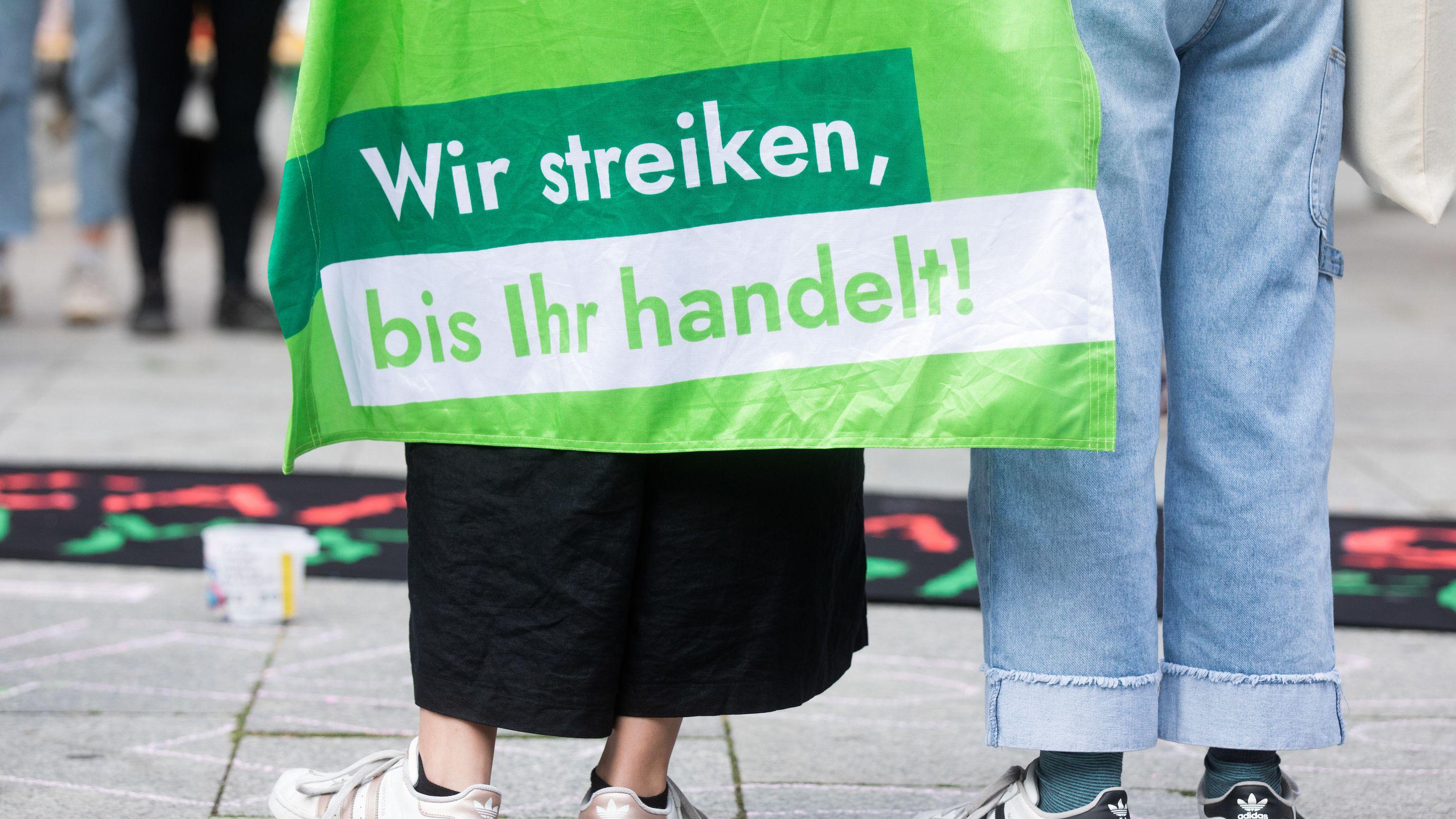 """Köln: Eine Schülerin trägt bei einer Fridays for Future Demonstration vor dem Hauptbahnhof eine Fahne mit der Aufschrift """"Wir streiken, bis Ihr handelt!""""."""