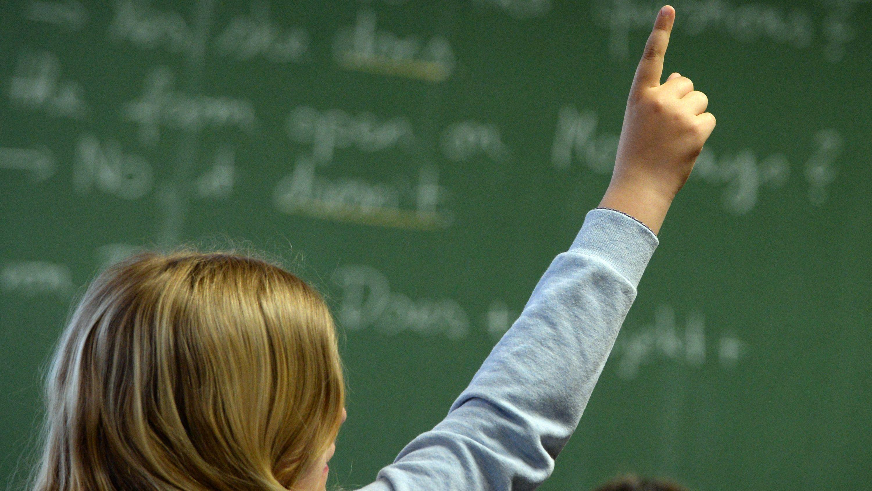 Eine Schülerin hebt den Finger im Unterricht