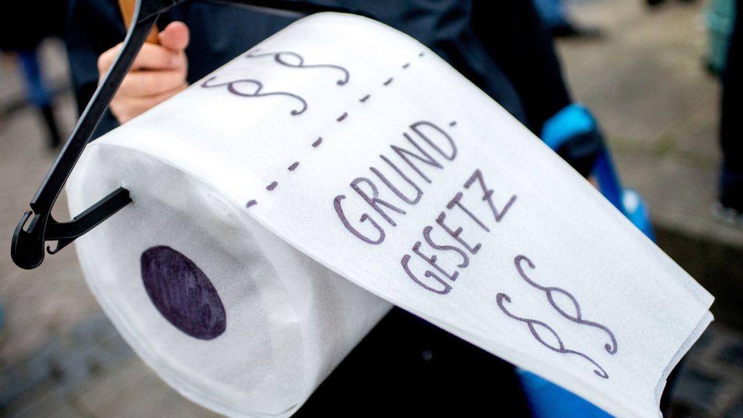 """Bei einer """"Querdenken""""-Demo hält eine Teilnehmerin eine gebastelte Toilettenpapierrolle mit der Aufschrift """"Grundgesetz"""" (Archivbild 21.11.20)"""