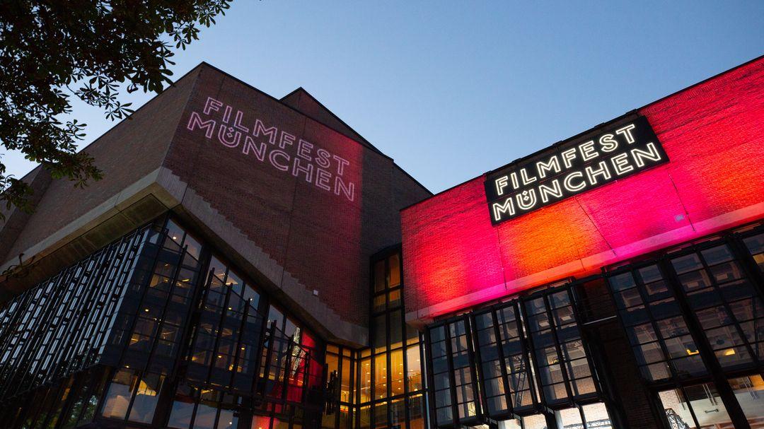 """Man sieht die Fassade des Münchner Kulturzentrums am Gasteig. Auf die Fassade ist die Schrift """"Filmfest München"""" projiziert."""