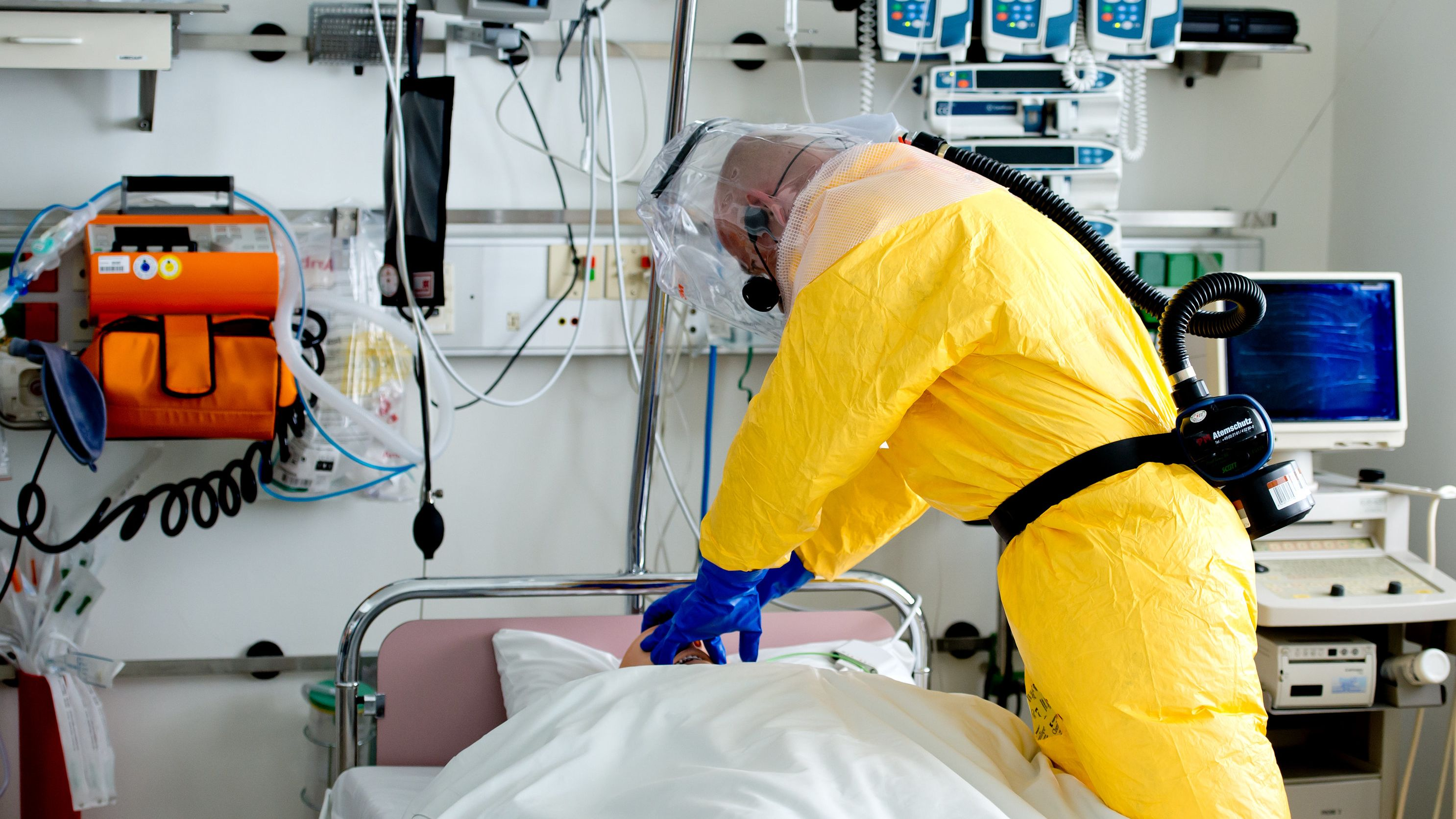 Ein Mann in Schutzausrüstung demonstriert die Versorgung eines Patienten auf einer Sonderisolierstation in einem Münchner Klinikum.