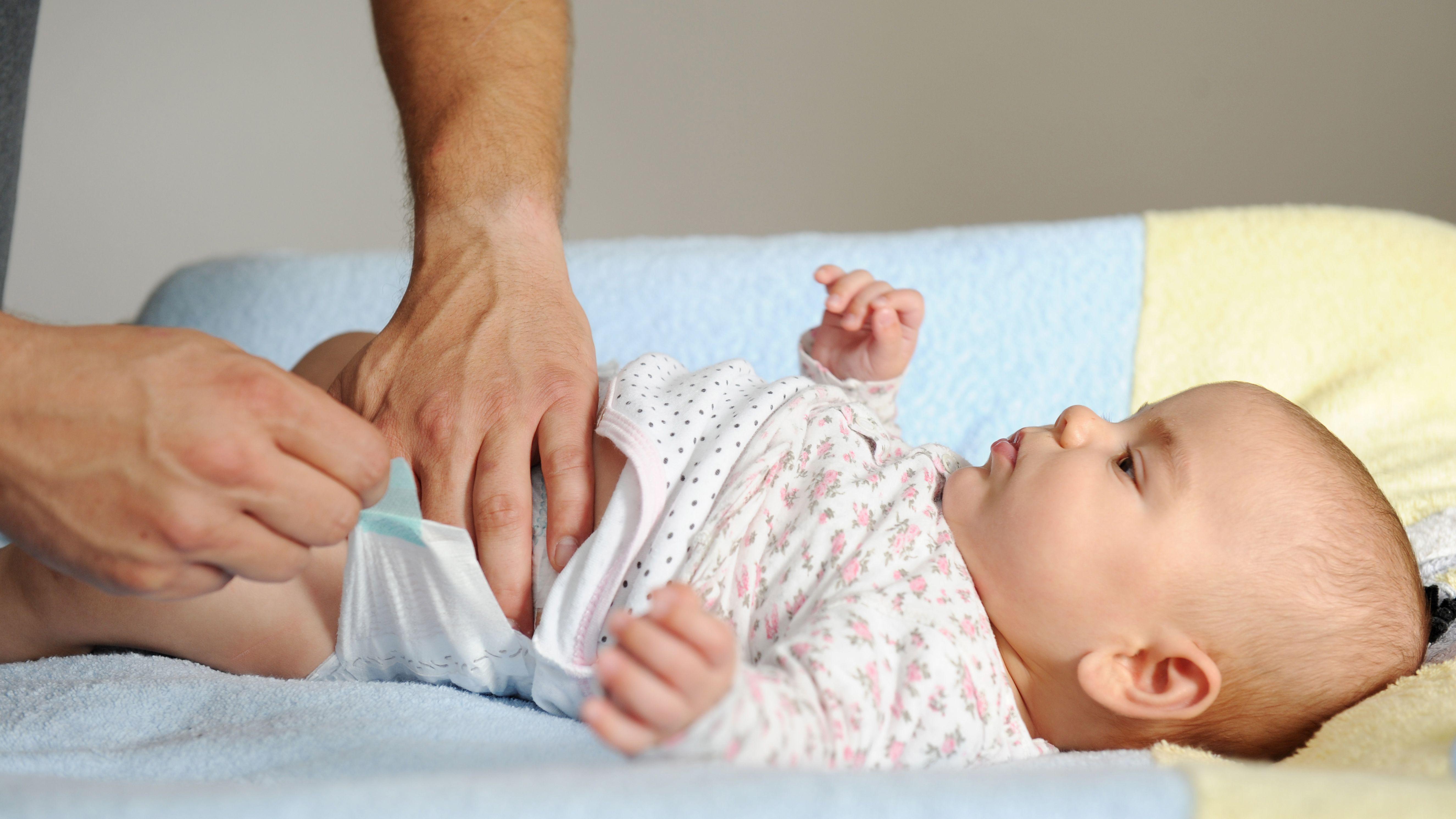 Ein Vater wickelt sein Baby