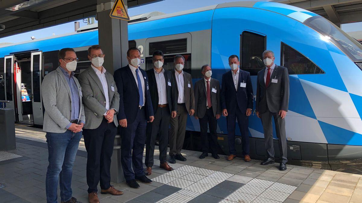 Acht Männer in Anzügen und mit FFP2-Masken stehen am Mühldorfer Bahnhof vor einem weiß-blauen Zug der Südostbayern-Bahn.