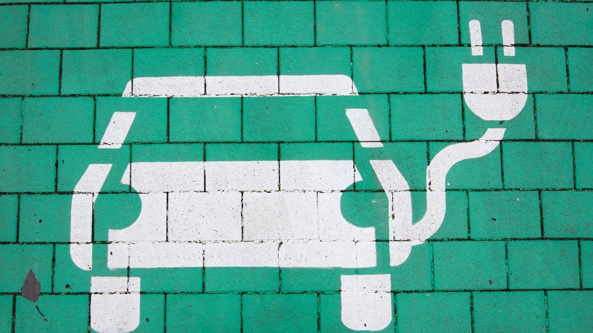 Auf einer grünen Mauer ist die Silhouette eines Elektroautos mit einem überdimensionalen Elektrostecker