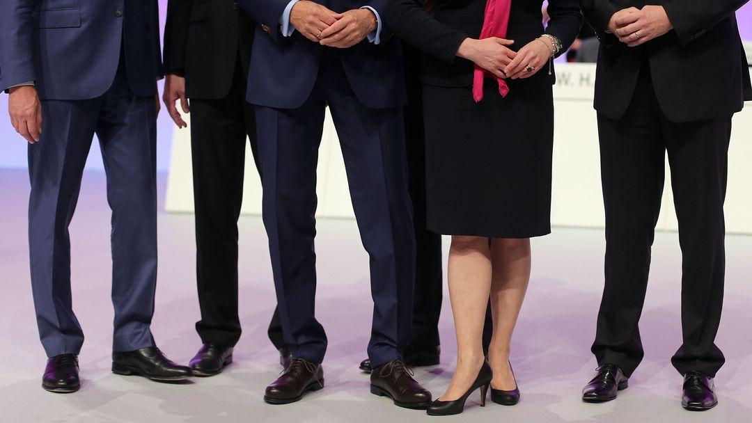 Mehrere männliche und ein weibliches Vorstandsmitglied stehen auf einer Hauptversammlung zusammen auf dem Podium.