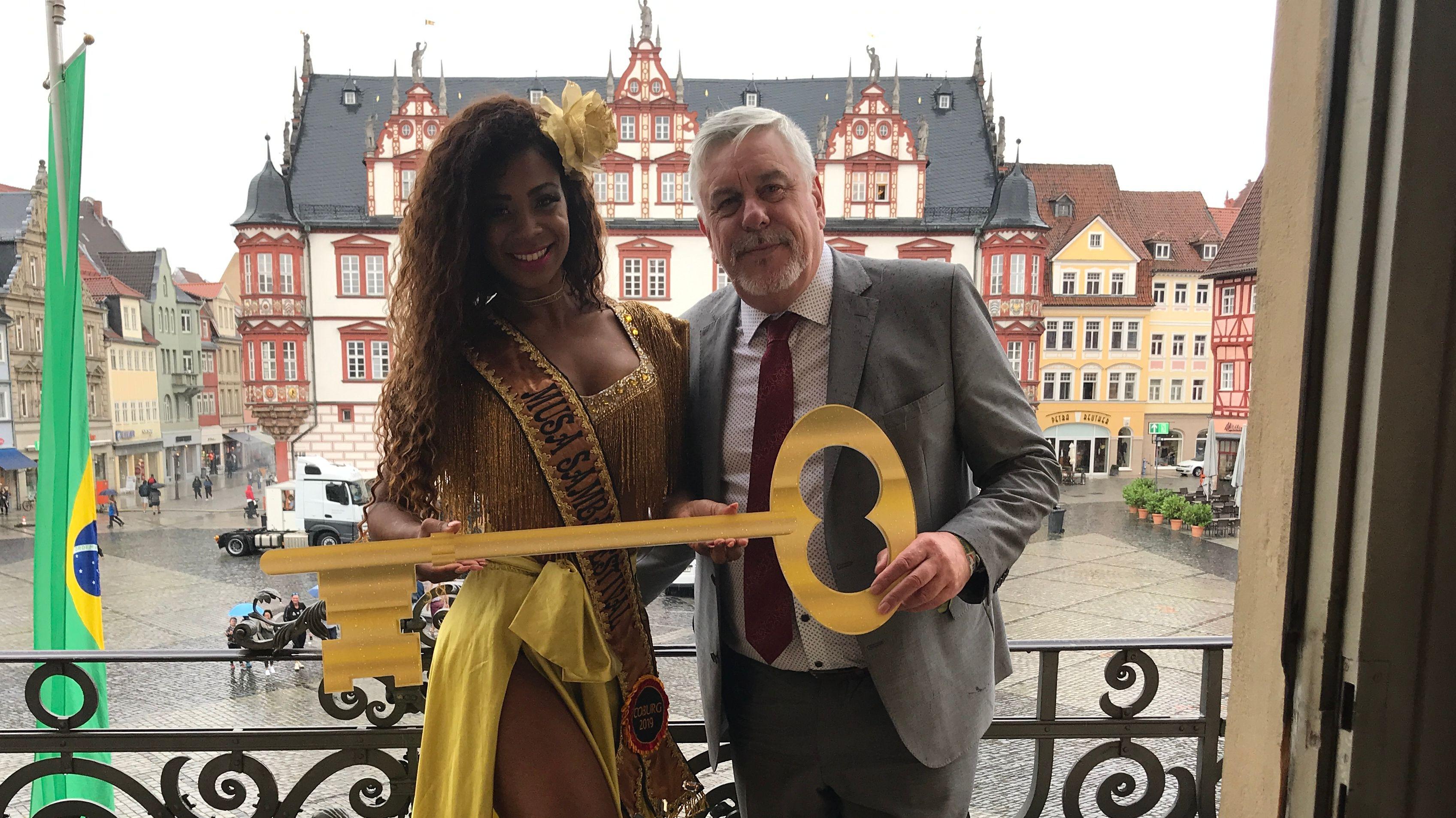 Eine Sambatänzerin in gelben Kleid bekommt einen überdimensional großen Schlüssel vom Oberbürgermeister der Stadt Coburg. Sie stehen auf dem Balkon des Rathauses.