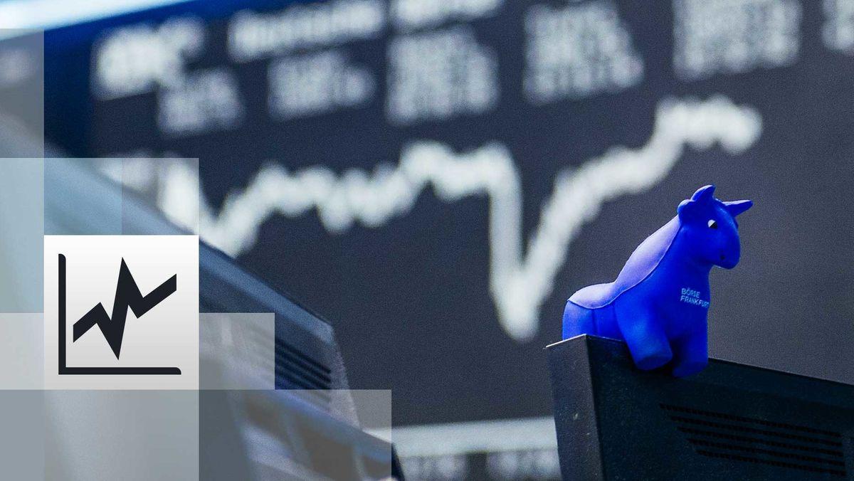 Ein blauer Stier aus Gummi sitzt auf der oberen Kante eines Bildschirmes, im Hintergrund die Kurstafel der Börse.
