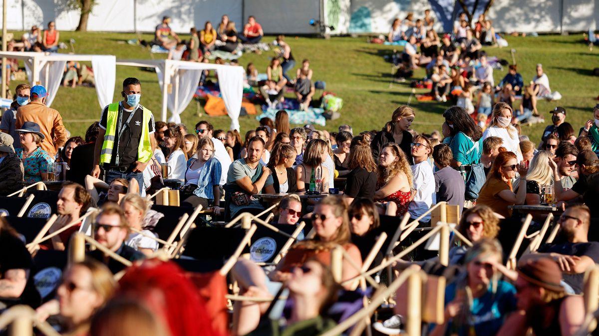 Dicht gedrängte Besucher auf einer Wiese sitzend oder in Liegestühlen, bei einem Event in der Bonner Rheinaue