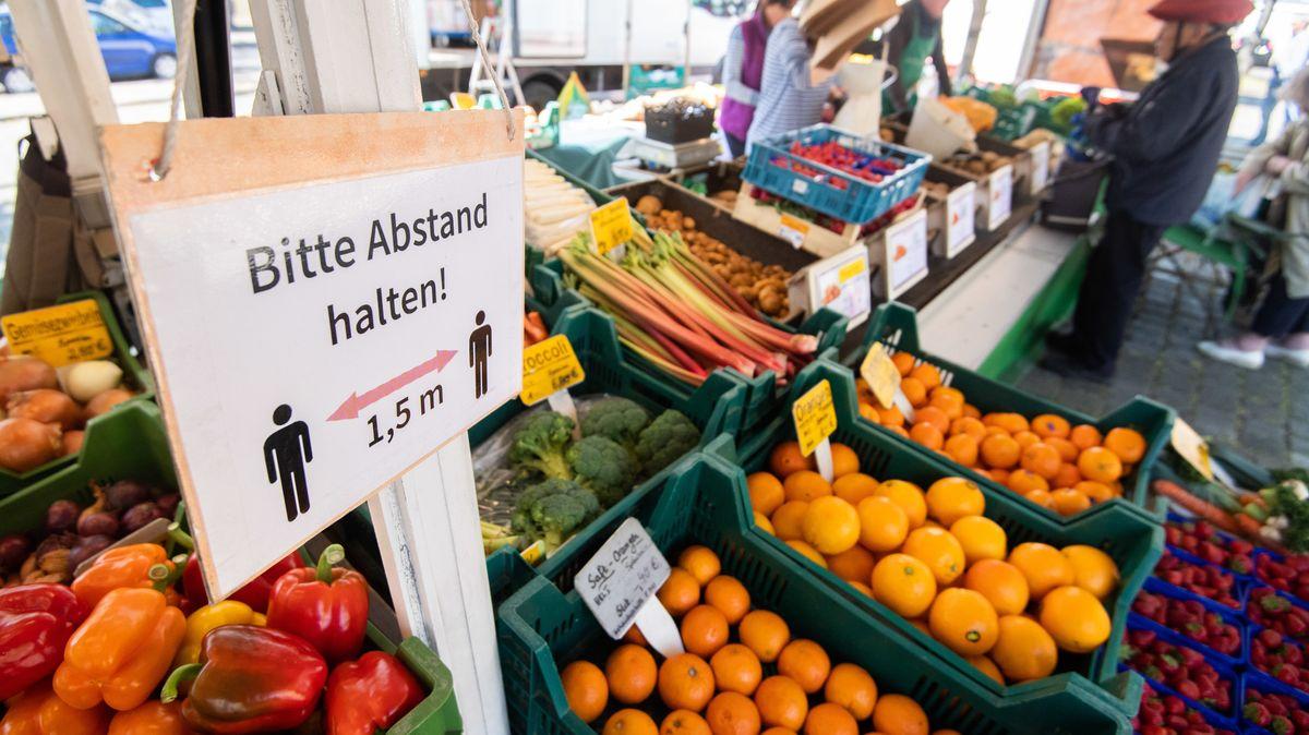 Obst und Gemüse auf einem Markt, dazwischen steht ein Hinweisschild, wegen des Coronavirus bitte 1,5 Meter Abstand zu halten
