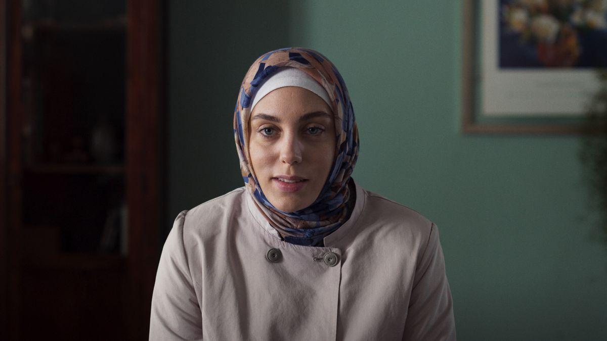 Eine junge türkische Frau in züchtig-ländlicher Kleidung schaut verlegen drein