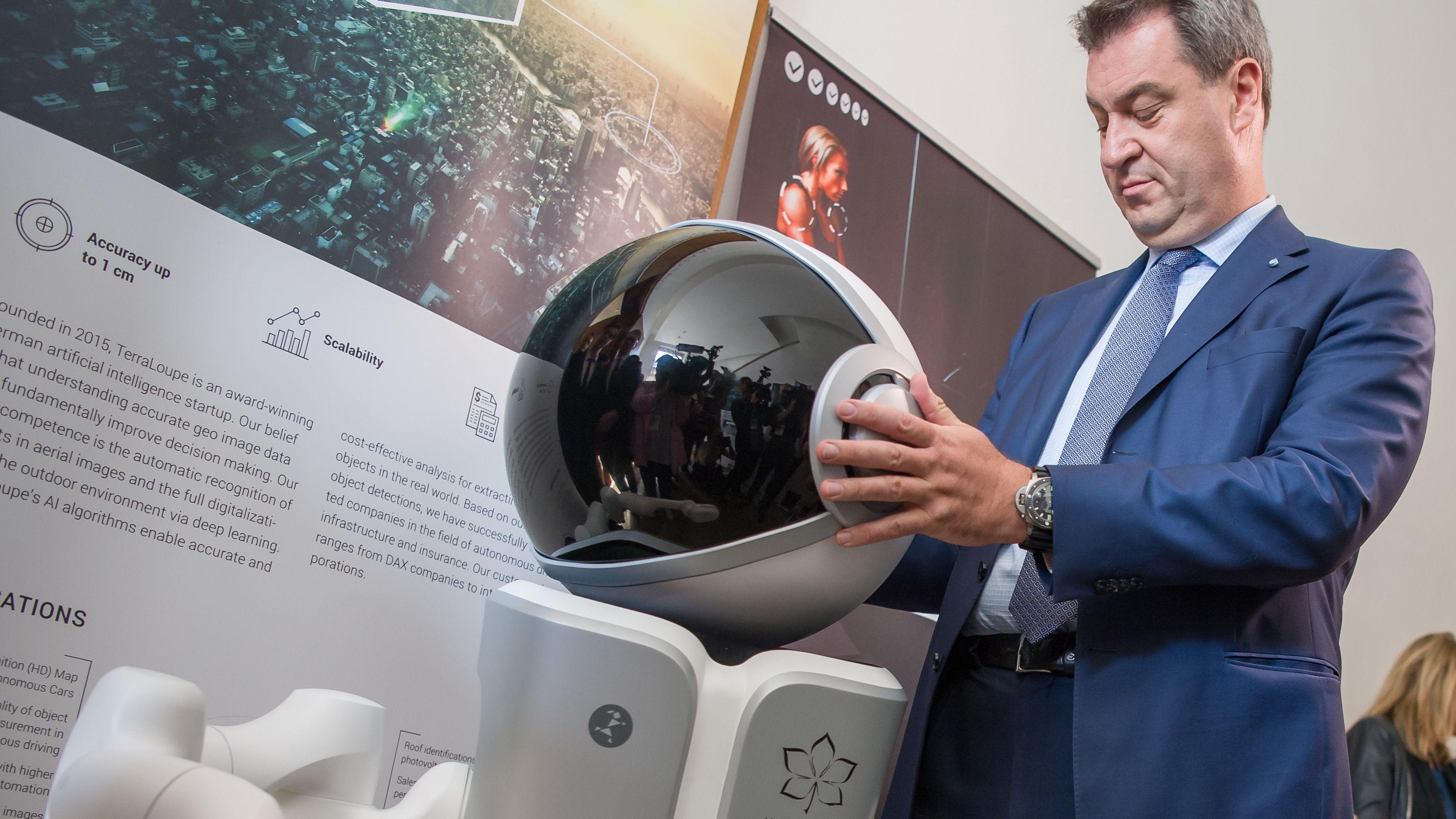 Ministerpräsident Markus Söder betrachtet einen Roboter.