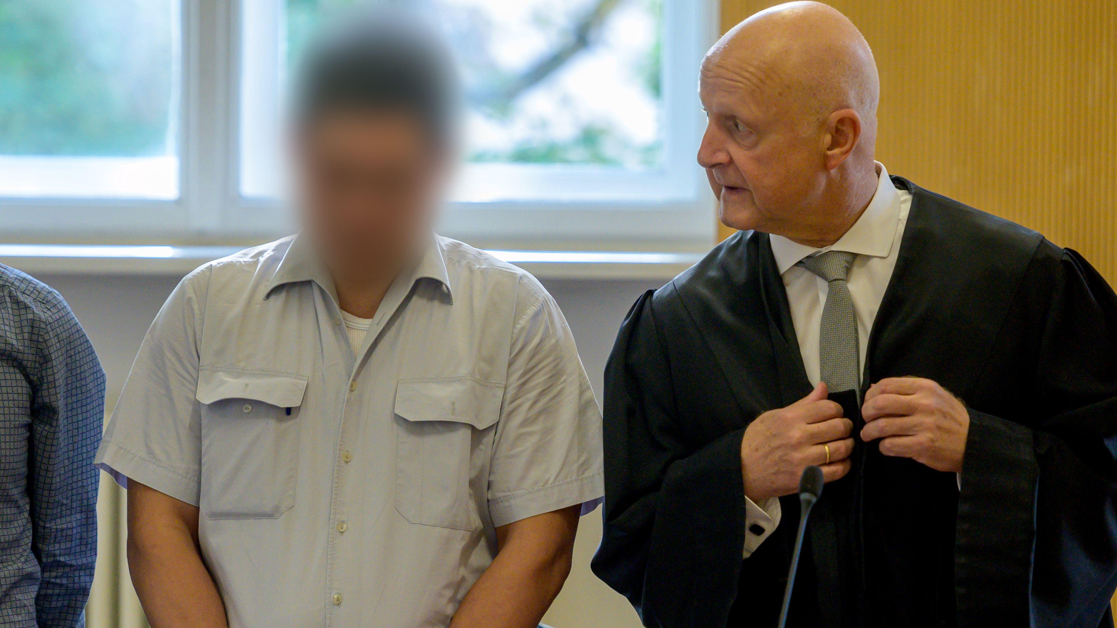 Der Angeklagte steht im Verhandlungssaal des Landgerichts Regensburg neben seinem Verteidiger Michael Haizmann.