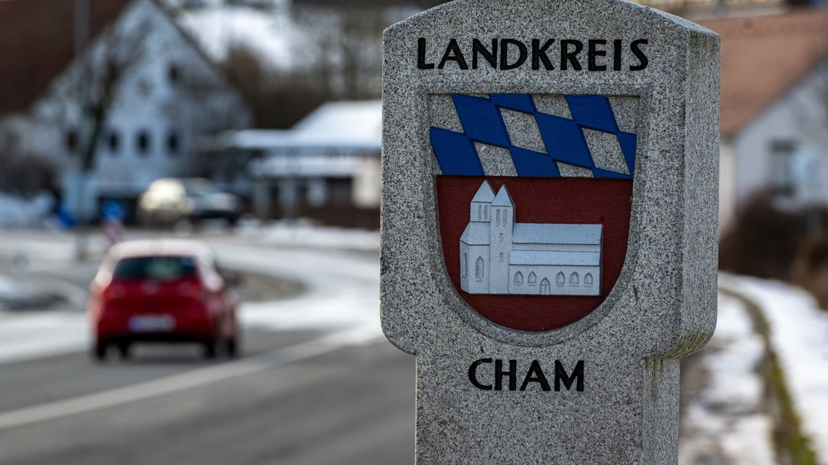 Ein Auto fährt an der deutsch-tschechischen Grenze an einem Stein mit dem Wappen des Landkreises Cham vorbei.