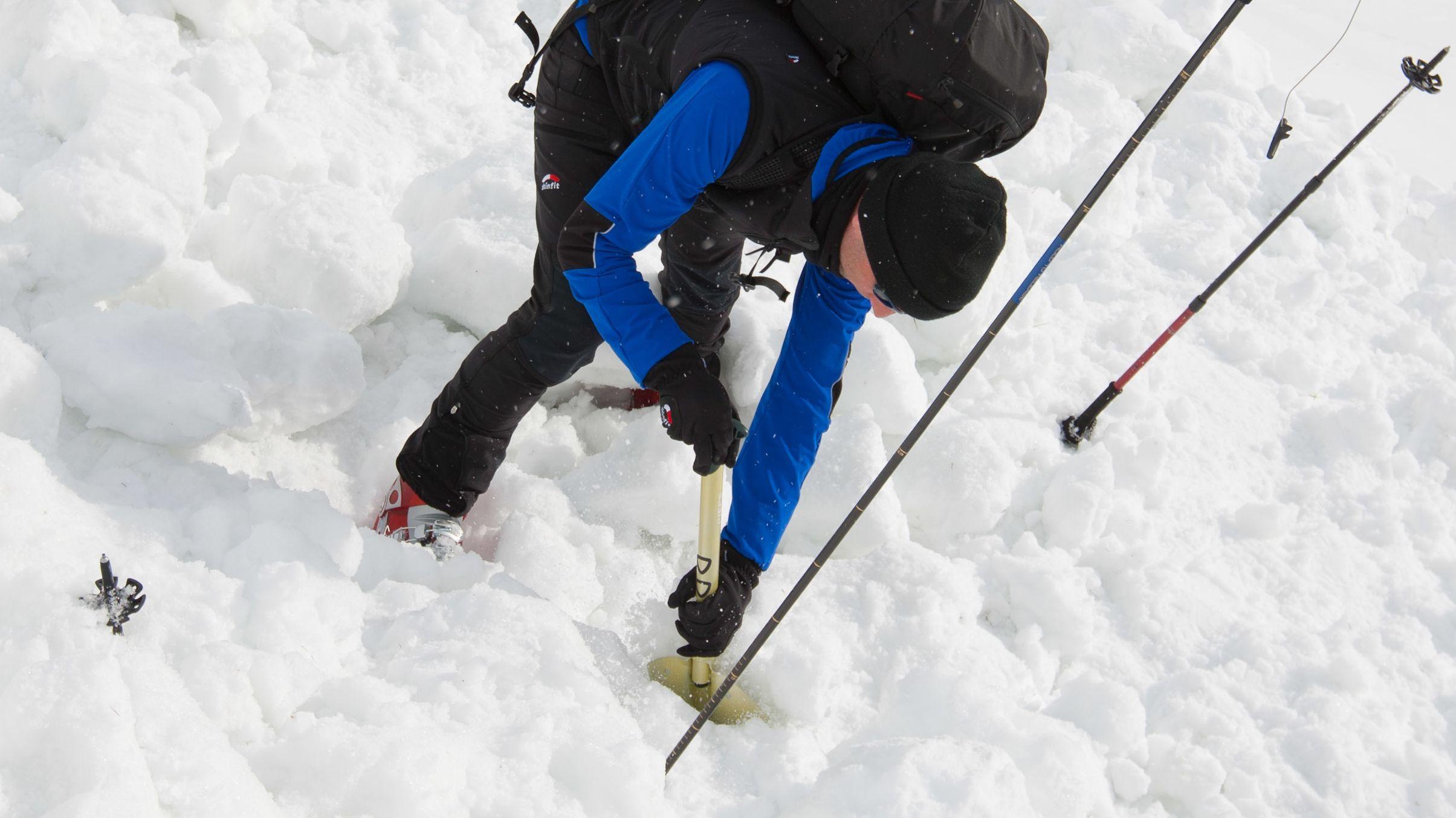 Mann gräbt im Schnee nach Verschütteten.