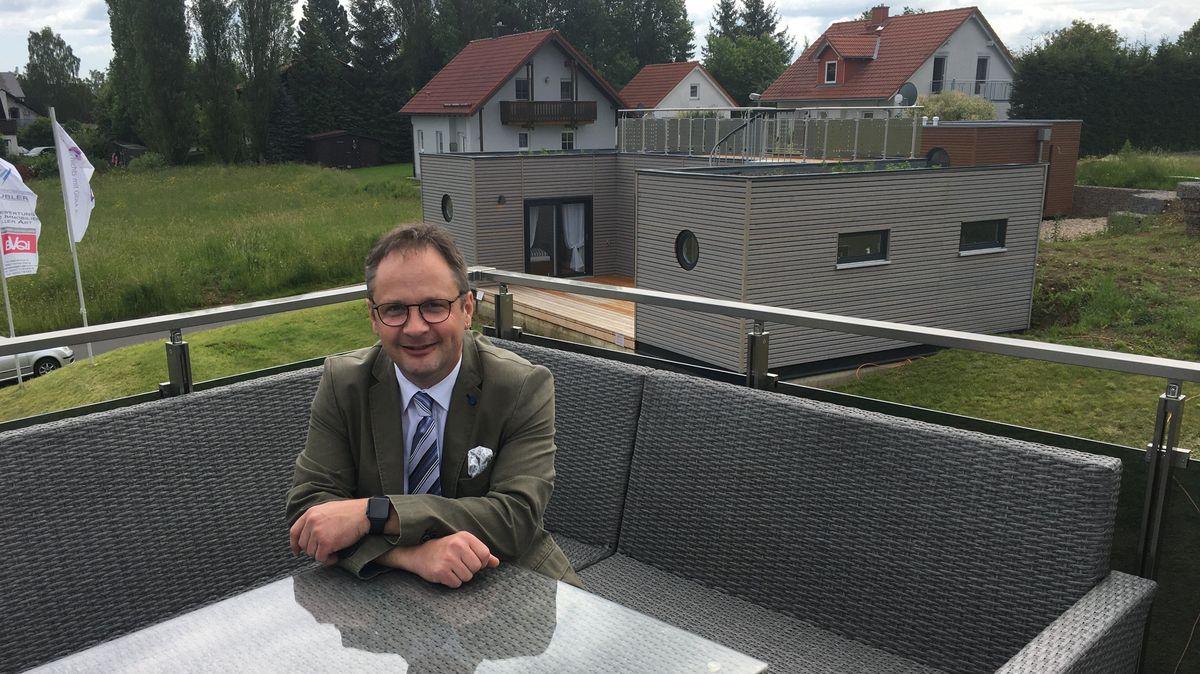 Andreas Übler sitzt vor einem Tiny House