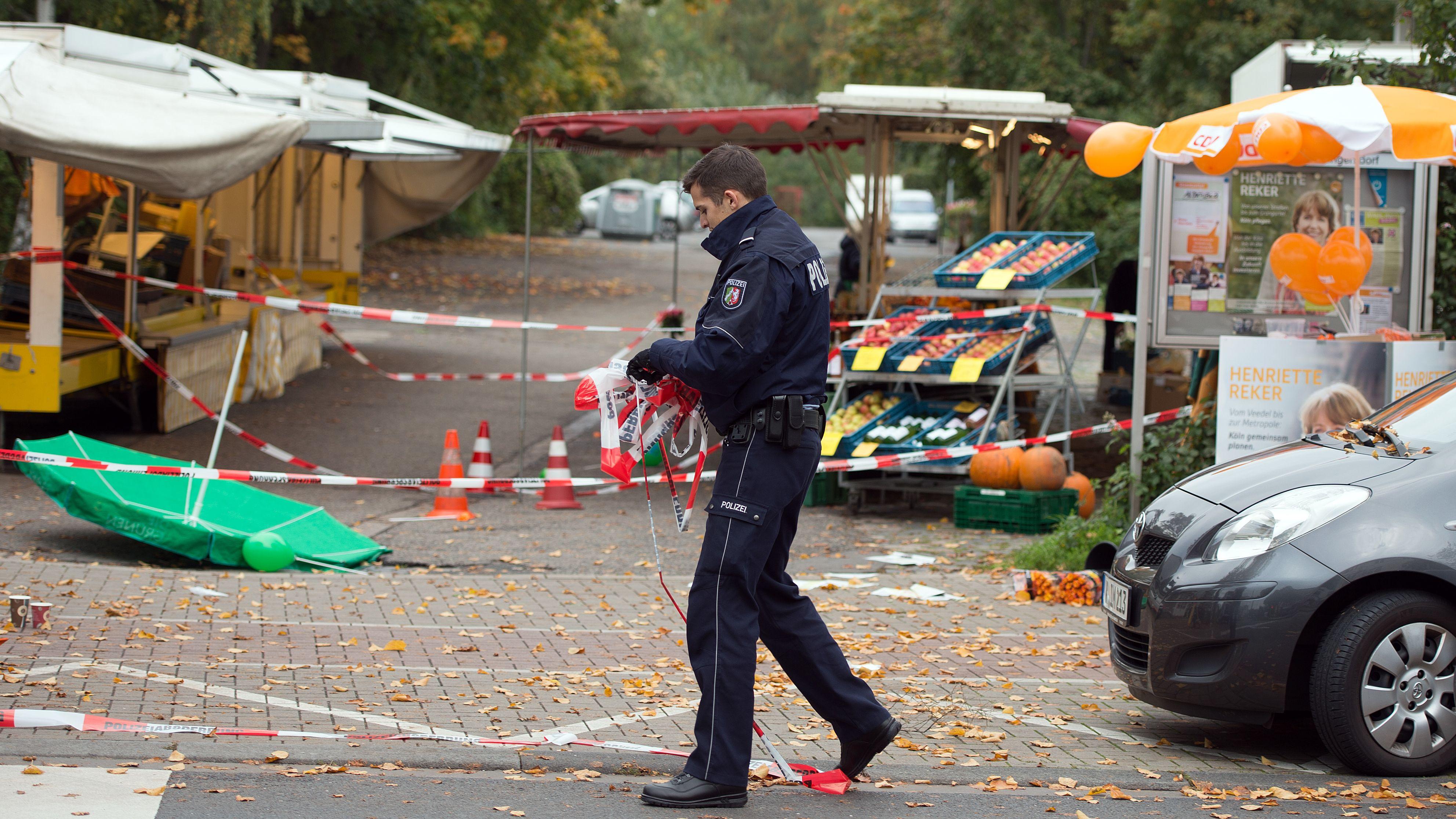 Ein Polizist wickelt am 17.10.2015 in Köln nach dem Attentat auf OB Reker Absperrband auf.