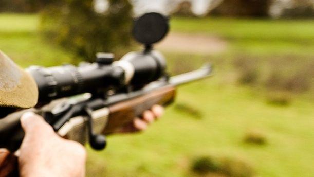 Ein Jäger zielt mit einem Jagdgewehr