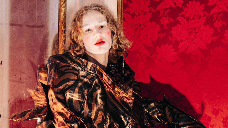 Ein Model lehnt gegen eine rote Wand. Das Gesicht ist weiß Geschminkt, die Lippen und Wangen rot. Das Model trägt einen Mantel mit Tigerprint.