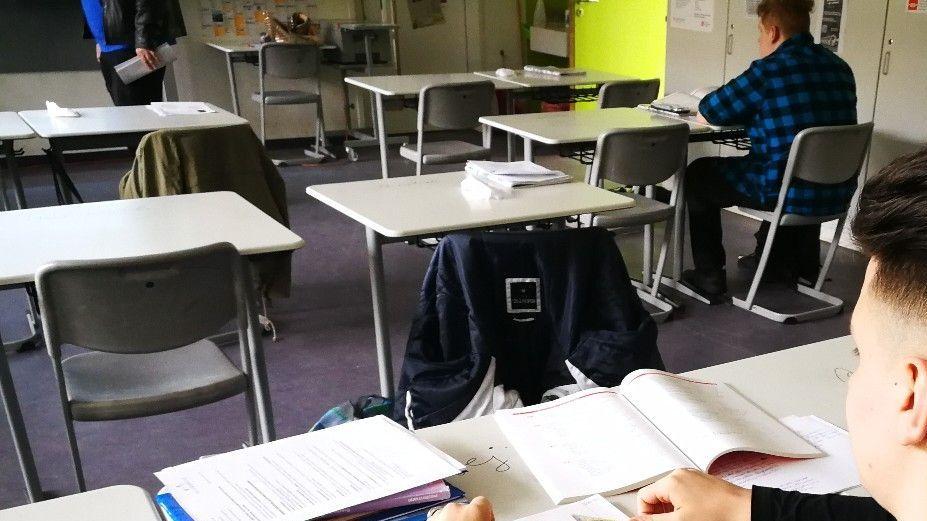 Schüler sitzen im Klassenzimmer unter Einhaltung der Abstandsregelungen