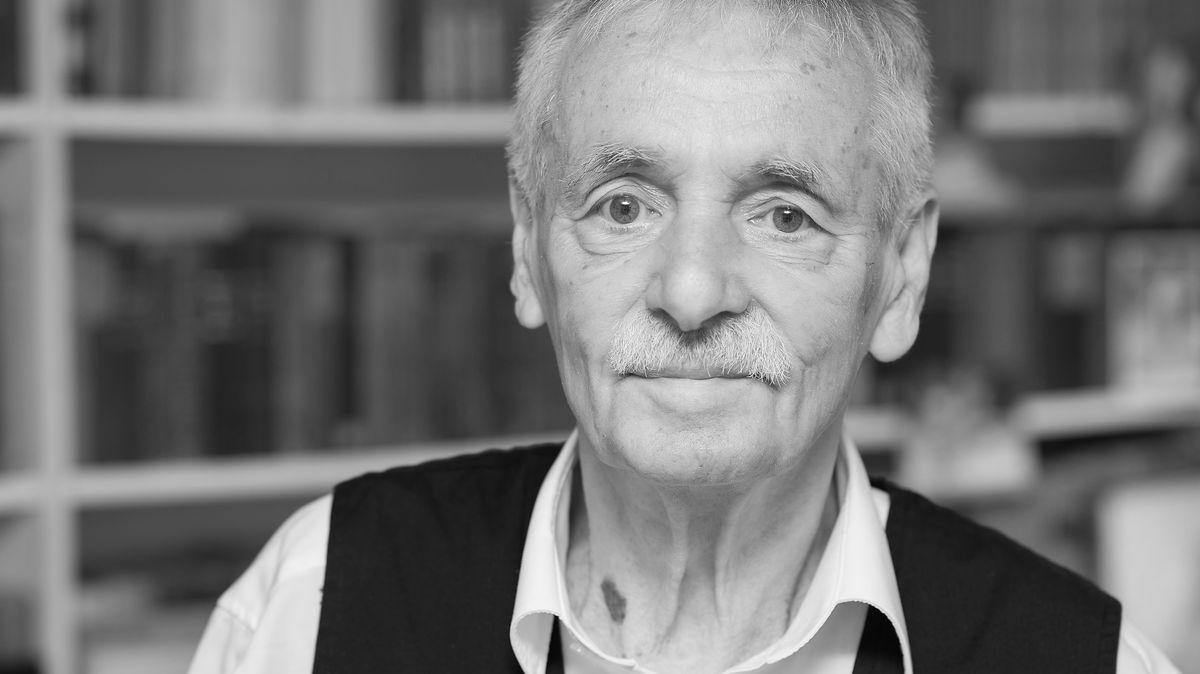 Guntram Vesper blickt, vor einem Bücherregal stehend, in die Kamera