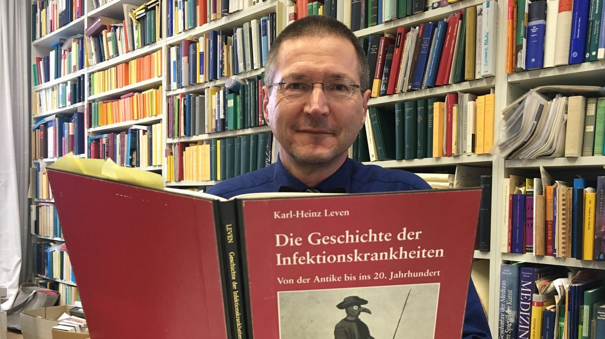 Ein Mann hält ein Geschichtsbuch