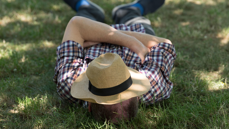 Mann liegt mit Hut über dem Gesicht im Gras