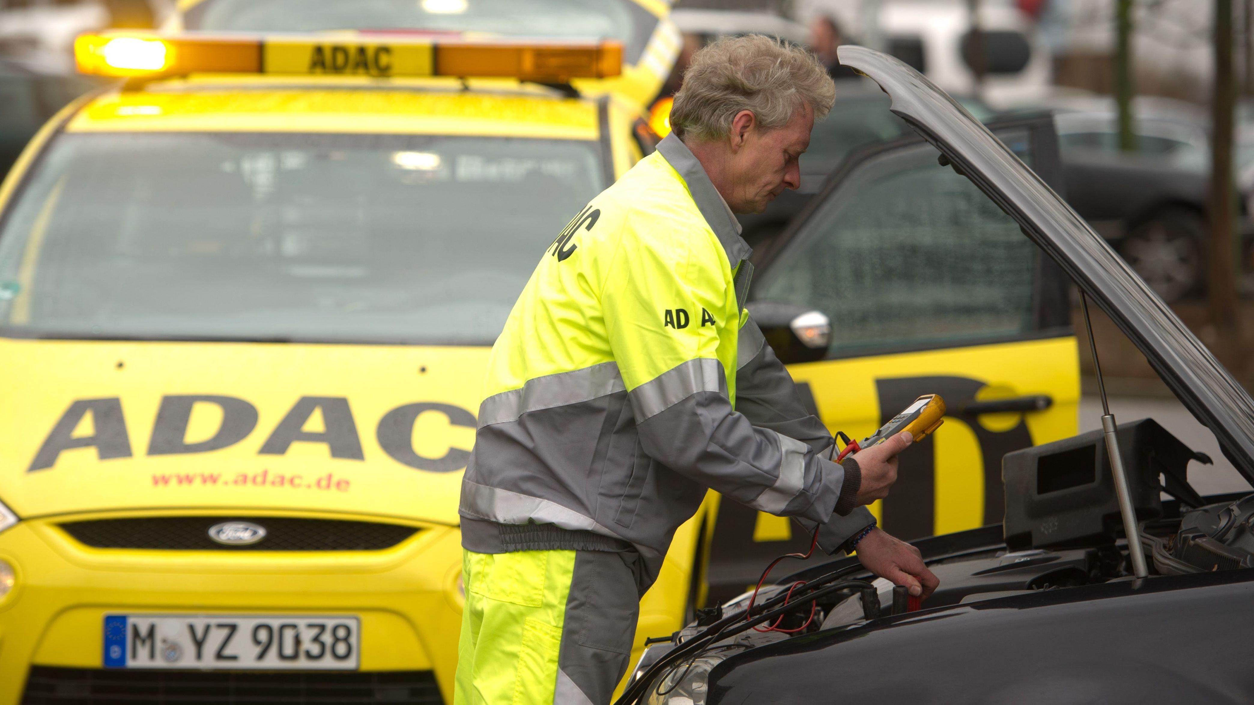 Ein ADAC-Straßenwachtfahrer überprüft die Batterieleistung an einem Fahrzeug.