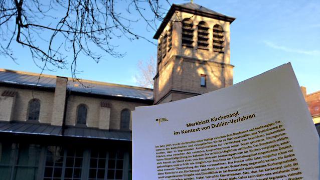 """Im Vordergrund das """"Merkblatt Kirchenasyl im Kontext von Dublin-Verfahren"""". Im Hintergrund die Himmelfahrtskirche in München Sendling."""