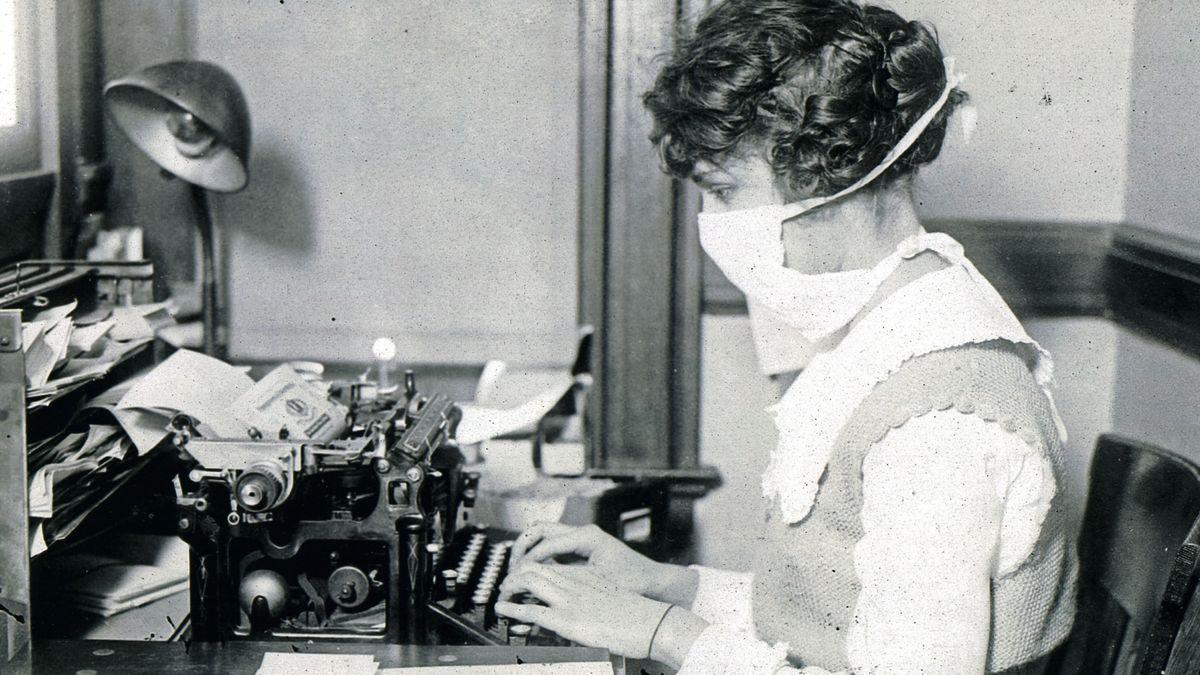 Schreibkraft im Jahr 1918 mit Mundschutz an der Schreibmaschine