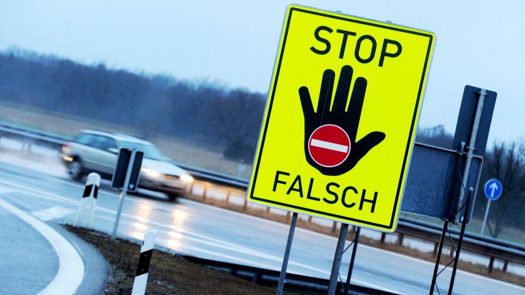 An einer Autobahnausfahrt warnt ein Schild vor dem Weiterfahren in die verkehrte Richtung.