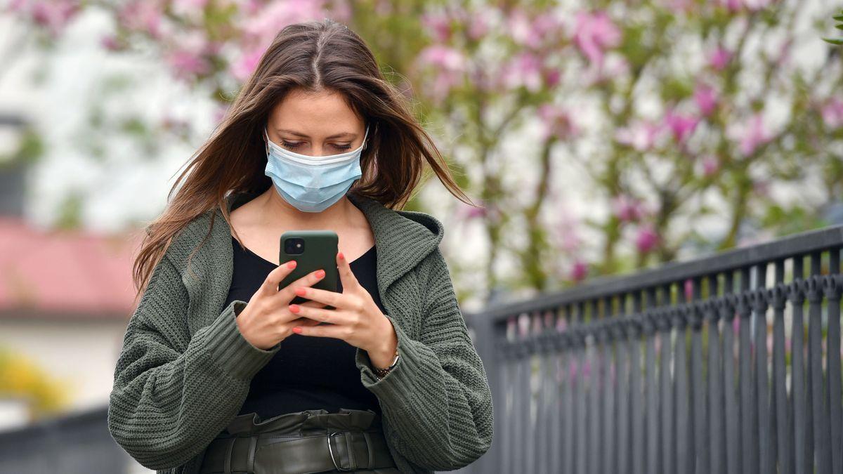 Junge Frau mit Mundschutz und Smartphone.