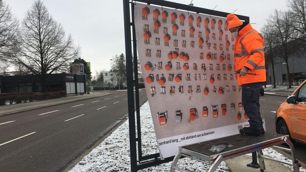 """An den Straßen werden Fotos der Ausstellung """"mit abstand am schoensten"""" in große Rahmen gespannt."""