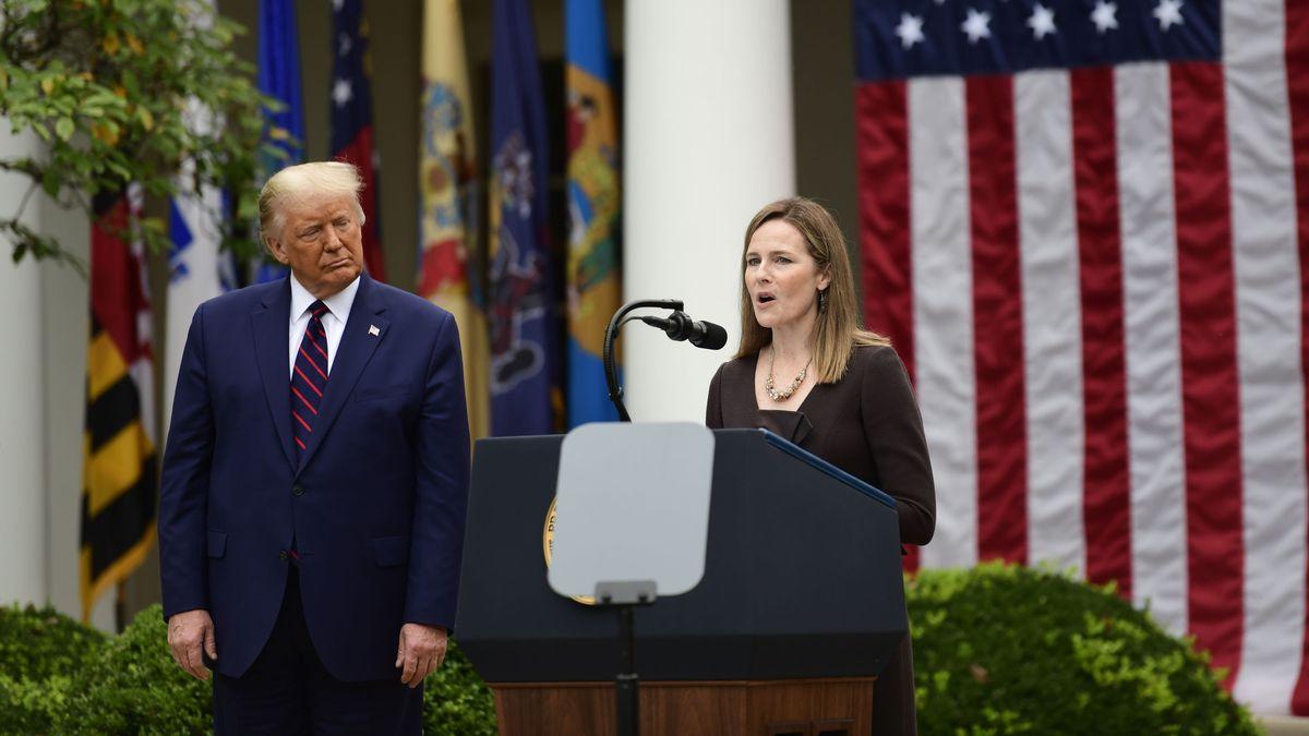 Amy Coney Barrett spricht an einem Rednerpult vor einer US-Flagge, neben ihr mit kritischem Blick Donald Trump.
