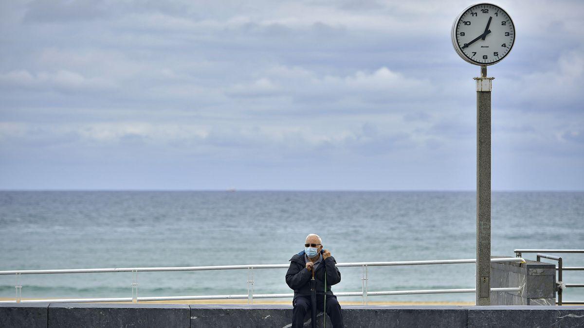 Ein Mann mit Mund-Nasen-Schutz sitzt auf einer Promenade am Strand von San Sebastian in Spanien.